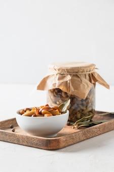 Cogumelos com mel em conserva em uma tigela e uma jarra em um fundo branco