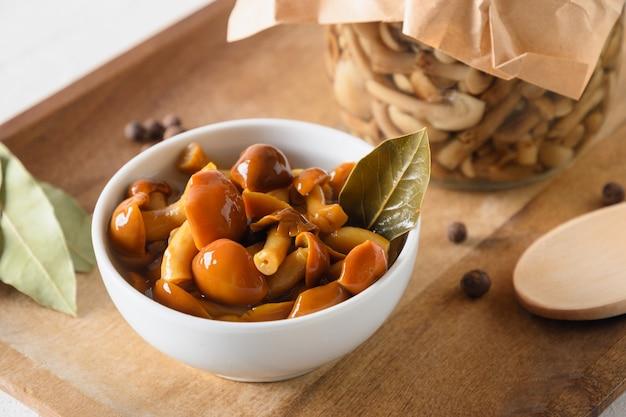 Cogumelos com mel em conserva servidos com folha de louro em uma tigela