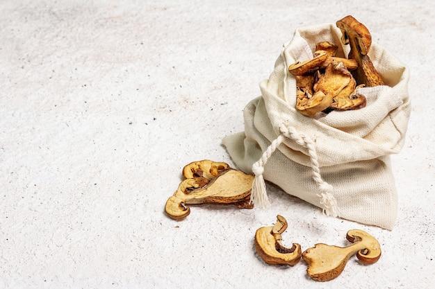 Cogumelos comestíveis secos da floresta em um saco de pano de saco isolado
