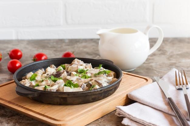 Cogumelos cozidos em creme de leite e salsa em uma frigideira em um suporte de madeira.