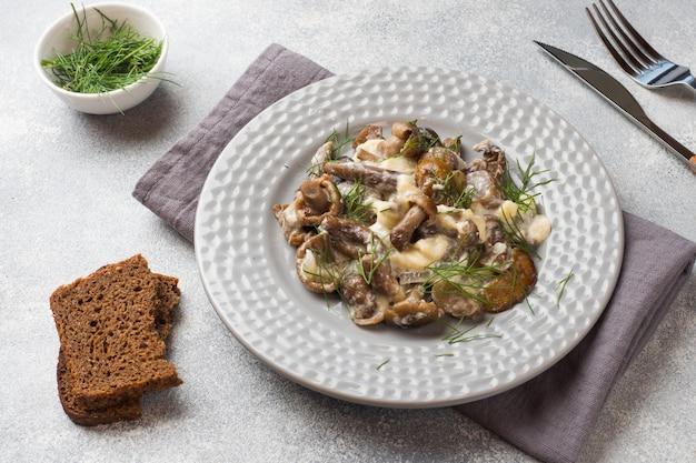 Cogumelos cozidos em molho com creme de leite e queijo em um prato