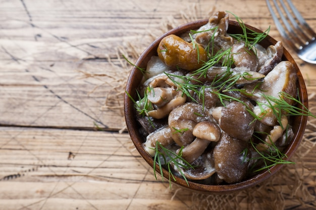 Cogumelos cozidos em um molho com creme de leite e queijo em uma tigela de madeira.