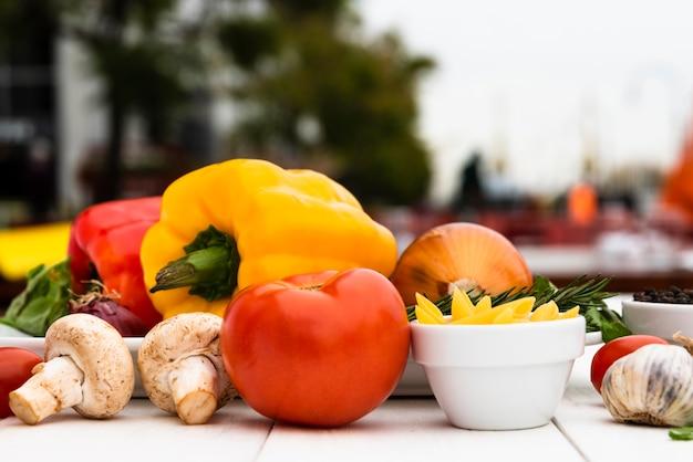 Cogumelos crus; tomate; pimentões; alho; cebola; na mesa branca