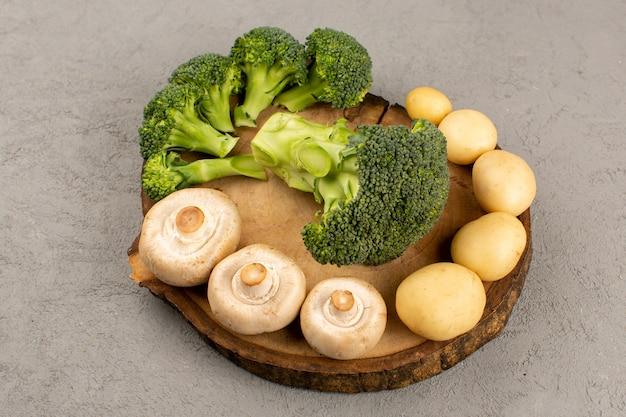 Cogumelos de brócolis verde vista superior e batatas no fundo cinza