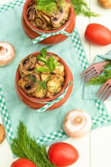 Cogumelos e batatas cozidos em uma panela de barro no forno de pedra.