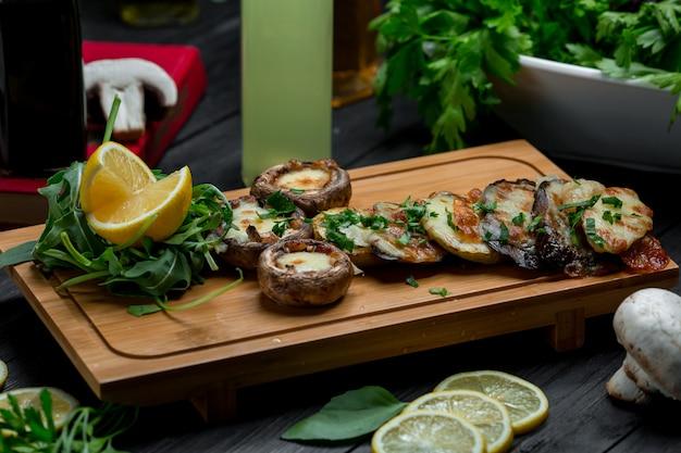 Cogumelos e batatas grelhados na placa de madeira