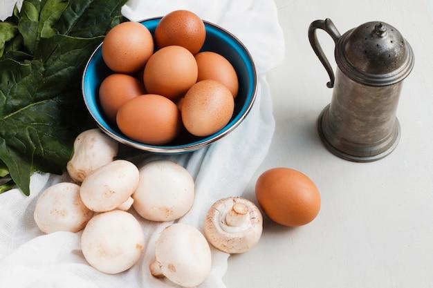 Cogumelos e ovos marrons de alto ângulo