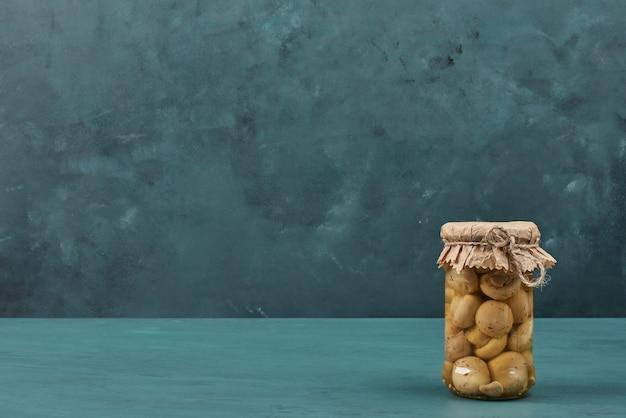 Cogumelos em conserva em uma jarra de vidro na mesa azul.