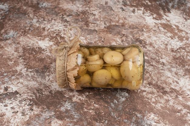 Cogumelos em conserva em uma jarra de vidro na mesa de mármore.