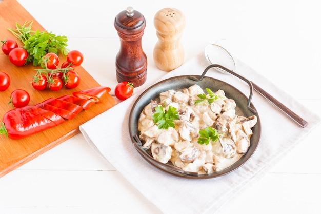 Cogumelos em molho de creme de leite em uma frigideira em um fundo branco. o conceito de comida deliciosa e saudável.
