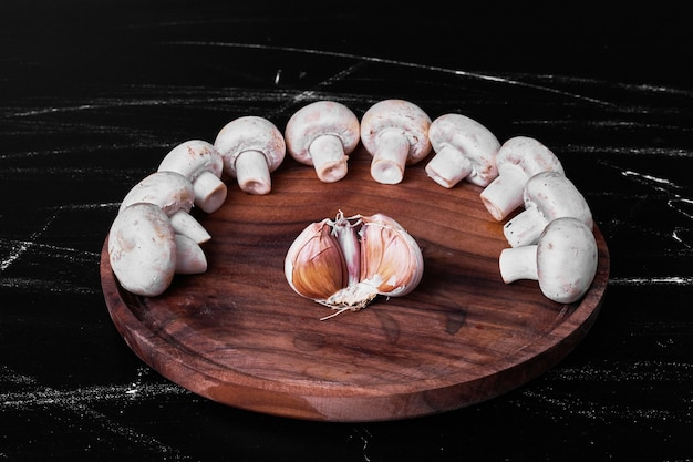 Cogumelos em travessa de madeira com dente de alho