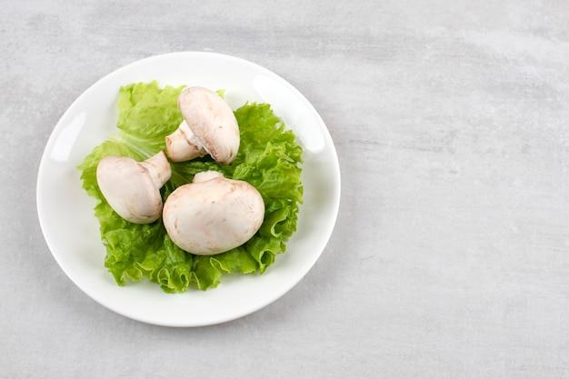 Cogumelos em uma folha de alface em um prato, na mesa de mármore.