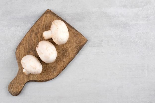 Cogumelos em uma placa de corte, na mesa de mármore.