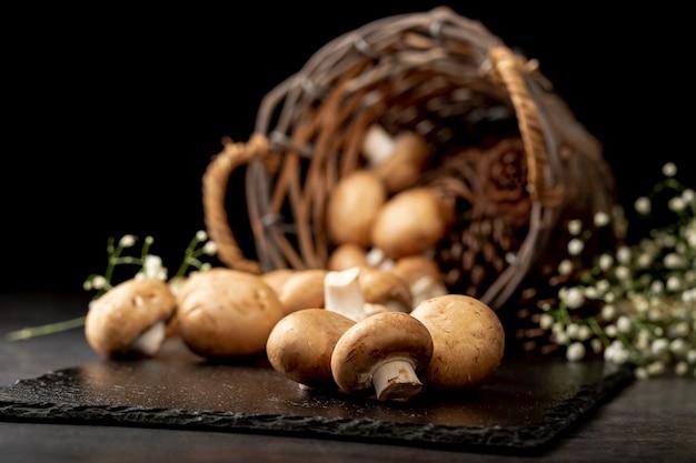 Cogumelos em uma placa de pedra preta com uma cesta de malha marrom
