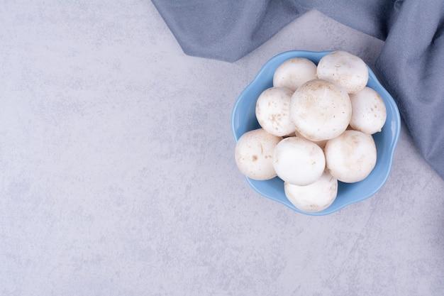 Cogumelos em uma xícara azul na superfície cinza