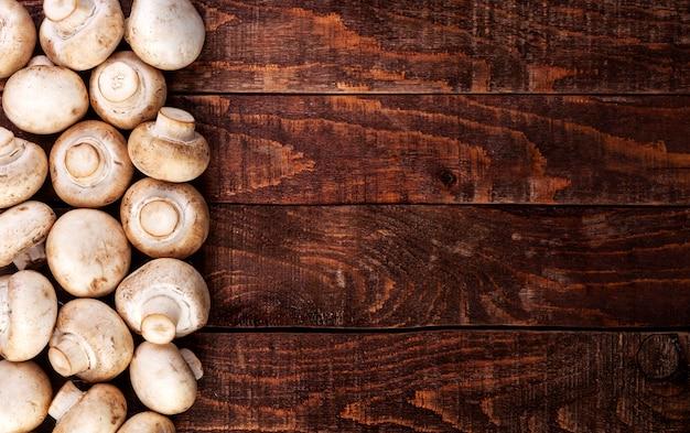Cogumelos frescos champignon na mesa de madeira