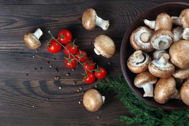 Cogumelos frescos, champignon, tomate e especiarias em uma mesa de madeira.