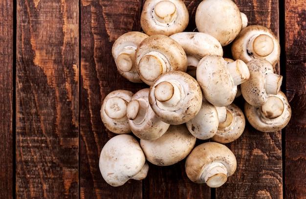 Cogumelos frescos do champignon na tabela de madeira, vista superior. copyspace