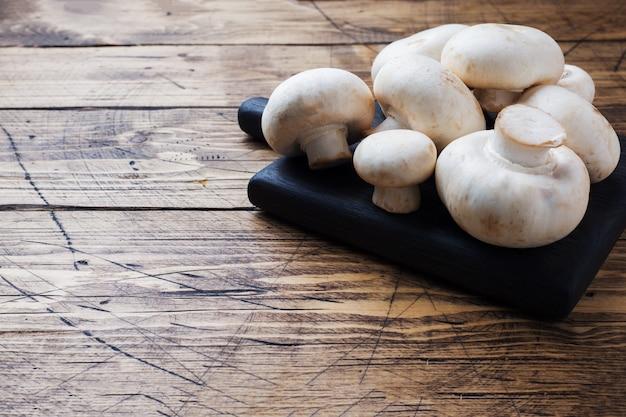 Cogumelos frescos dos cogumelos em um fundo de madeira.