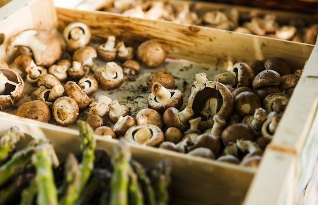 Cogumelos frescos na bandeja de madeira no mercado dos fazendeiros