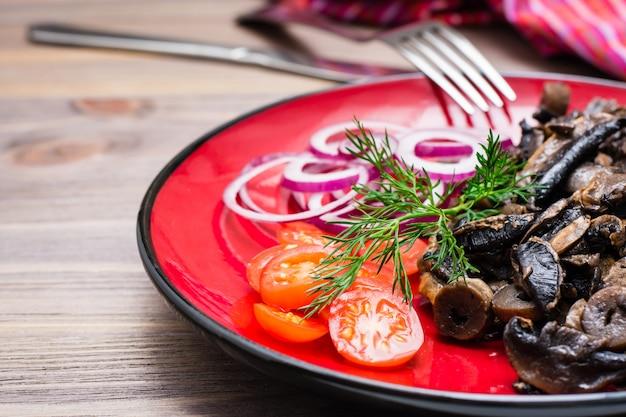 Cogumelos fritos, cebola e tomate cereja em um prato sobre uma mesa de madeira