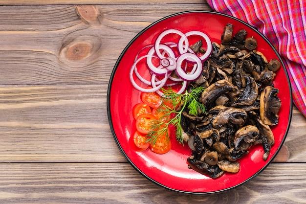 Cogumelos fritos, cebola e tomate cereja no prato na mesa de madeira. vista do topo