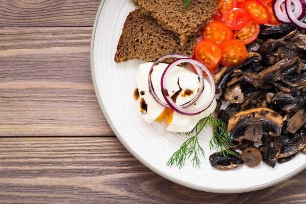 Cogumelos fritos, ovo escalfado, tomate, cebola e endro em um prato sobre uma mesa de madeira