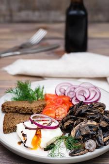 Cogumelos fritos, ovo pochê, tomate, cebola e endro no prato na mesa de madeira