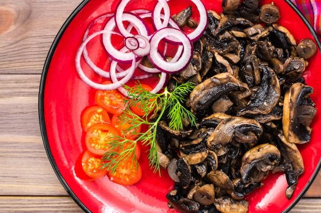 Cogumelos fritos, tomate cereja e cebola em um prato em uma mesa de madeira. vista do topo