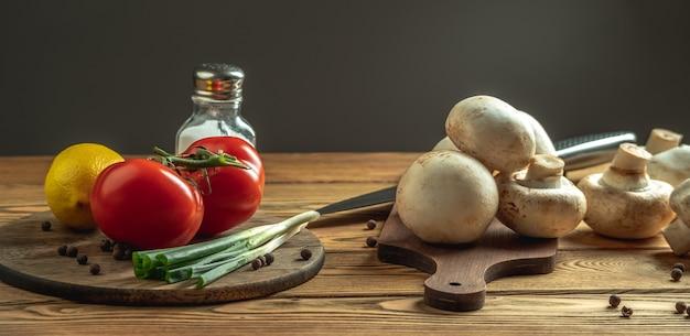 Cogumelos, legumes, limão e especiarias em uma mesa de madeira. conceito de ingredientes para cozinhar um prato delicioso.