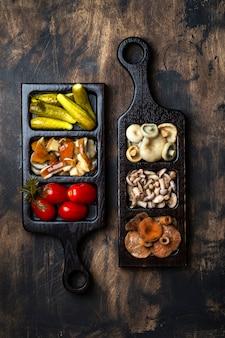 Cogumelos marinados e vegetais em uma mesa de madeira