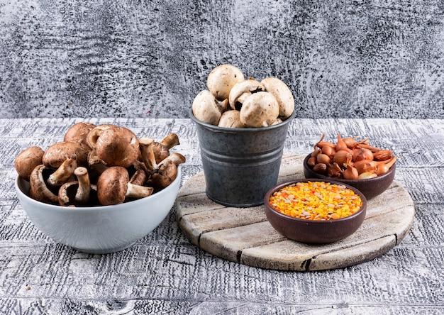 Cogumelos marrons em uma tigela e um dinheirinho com lentilhas, cebola pequena em tigelas vista lateral