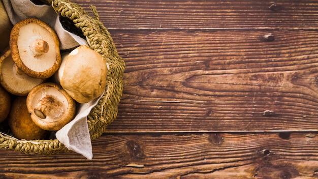 Cogumelos na cesta na mesa de madeira
