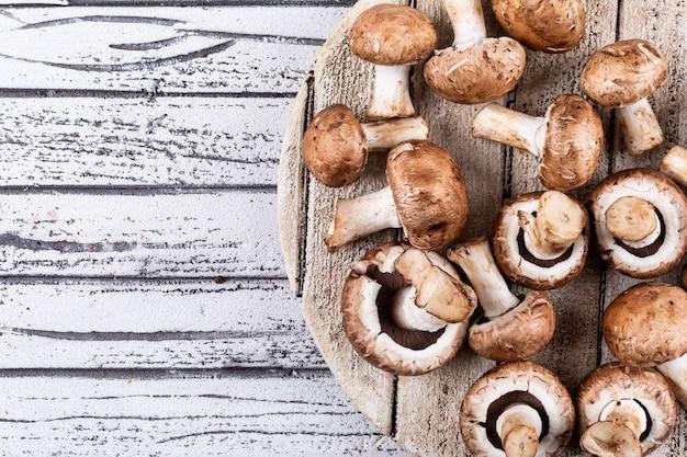 Cogumelos na tábua sobre uma mesa de madeira clara