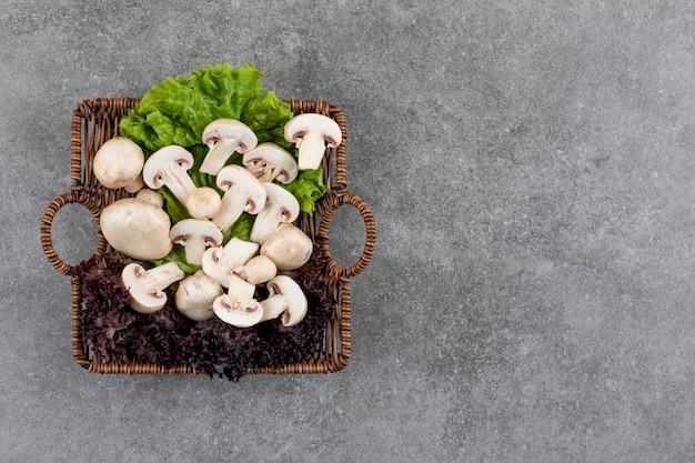 Cogumelos orgânicos frescos com verduras em uma cesta sobre uma superfície cinza