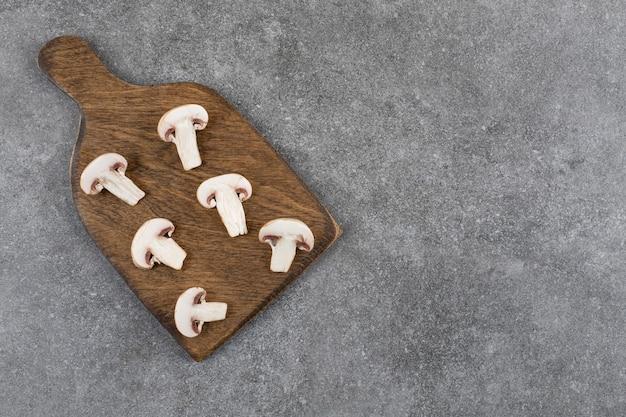 Cogumelos orgânicos picados em uma placa de madeira