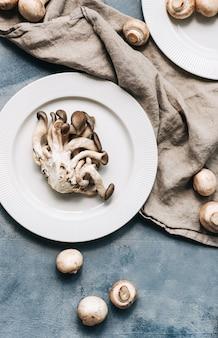 Cogumelos ostra frescos em chapa branca com tecido de linho, copie o espaço. vista do topo.
