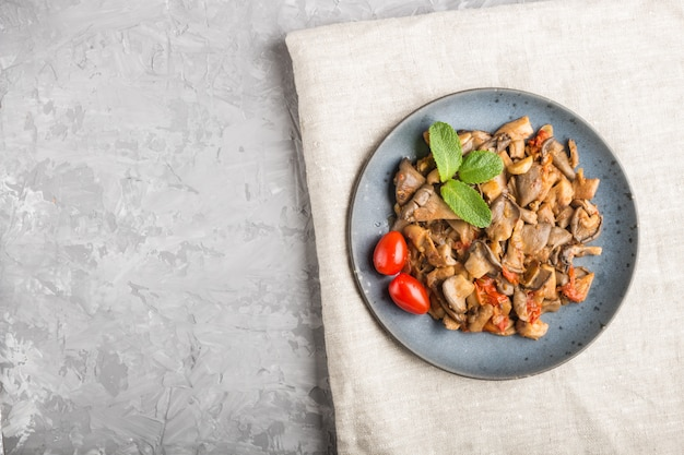 Cogumelos ostra fritos com tomate no fundo cinza de concreto