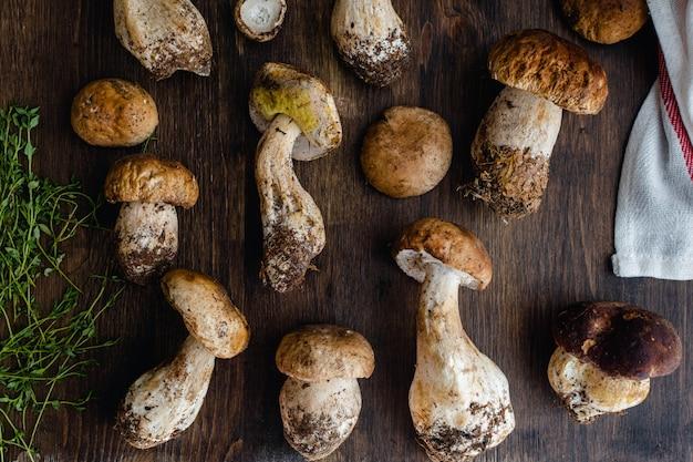 Cogumelos porcini comestíveis crus na superfície de madeira escura rústica
