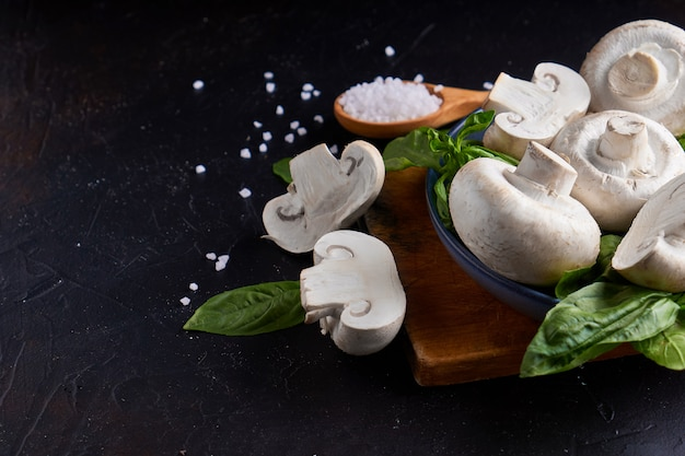Cogumelos portobello brancos champignon grande com manjericão no prato sobre fundo escuro de pedra