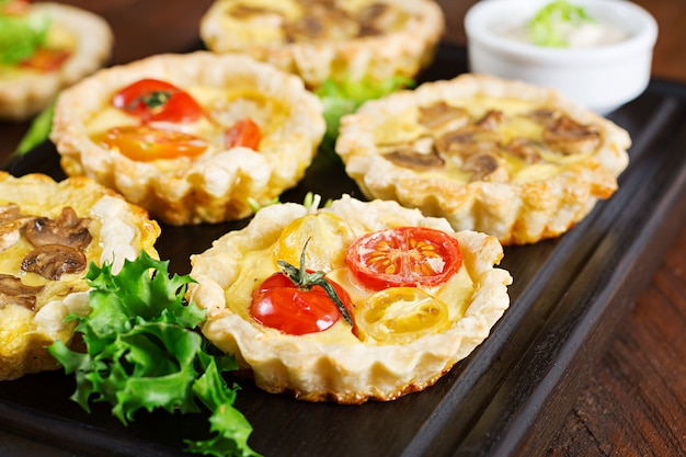 Cogumelos, queijo cheddar, tortinhas de tomate em madeira