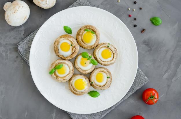 Cogumelos recheados com ovos de codorna em um prato branco com folhas de manjericão e tomilho