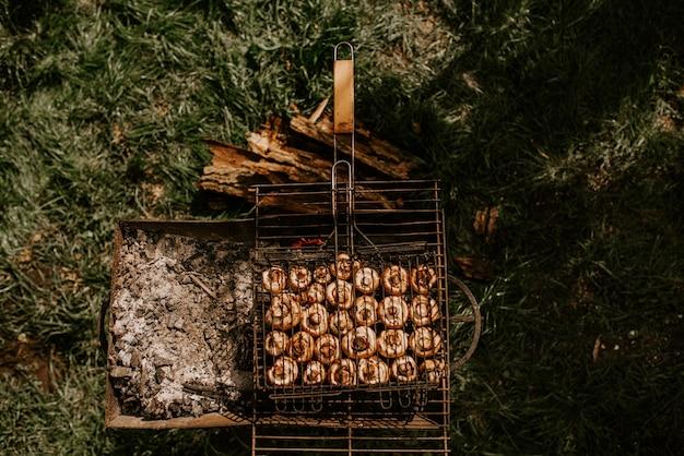 Cogumelos redondos de cogumelos pequenos brancos idênticos empilhados em fileiras regulares em um churrasco na grelha. fundo da grama verde. verão. fumaça branca sobre vegetais assados.