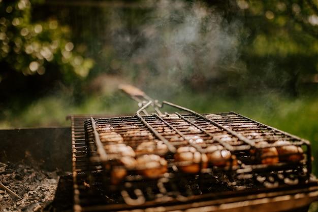 Cogumelos redondos de cogumelos pequenos brancos idênticos empilhados em fileiras regulares em um churrasco na grelha.