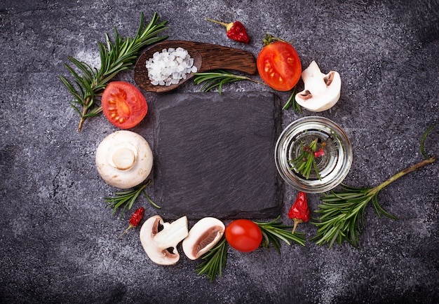 Cogumelos, tomates, alecrim, sal e azeite. fundo de alimentos. vista do topo