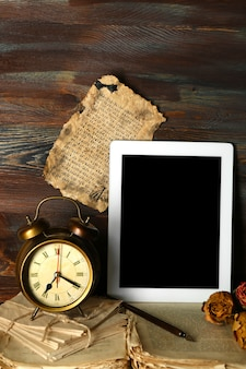 Coisas antigas e tablet na mesa de madeira