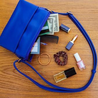 Coisas da bolsa de senhora aberta. bolsa feminina na superfície de madeira. cosméticos e acessórios femininos caíram da bolsa azul.