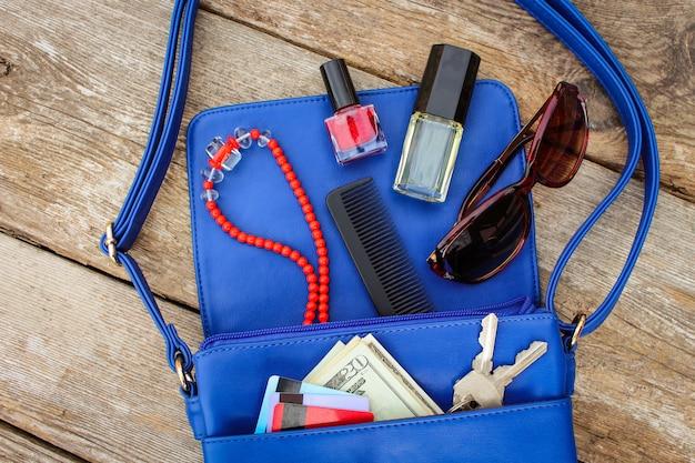 Coisas da bolsa de senhora aberta. cosméticos, dinheiro e acessórios femininos caíram da bolsa azul.
