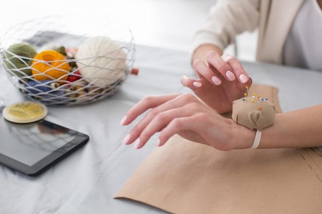 Coisas de alfaiates. close-up da mão feminina suave tirando o alfinete do travesseiro enquanto costura Foto Premium