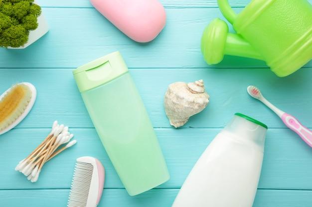 Coisas de bebê de foto plana leigos. esponja, sabonete, gel de banho, pato de borracha, pente azul. vista superior de cosméticos para bebês